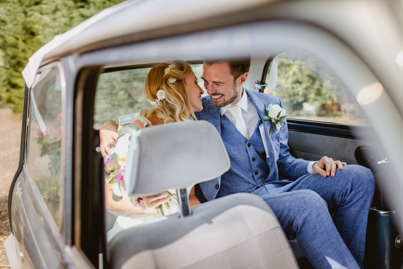 bride and groom kissing on the backseat of a mini