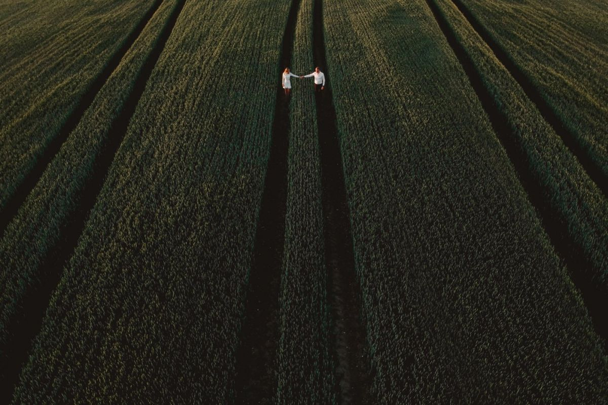 bride and groom to be in field drone photo