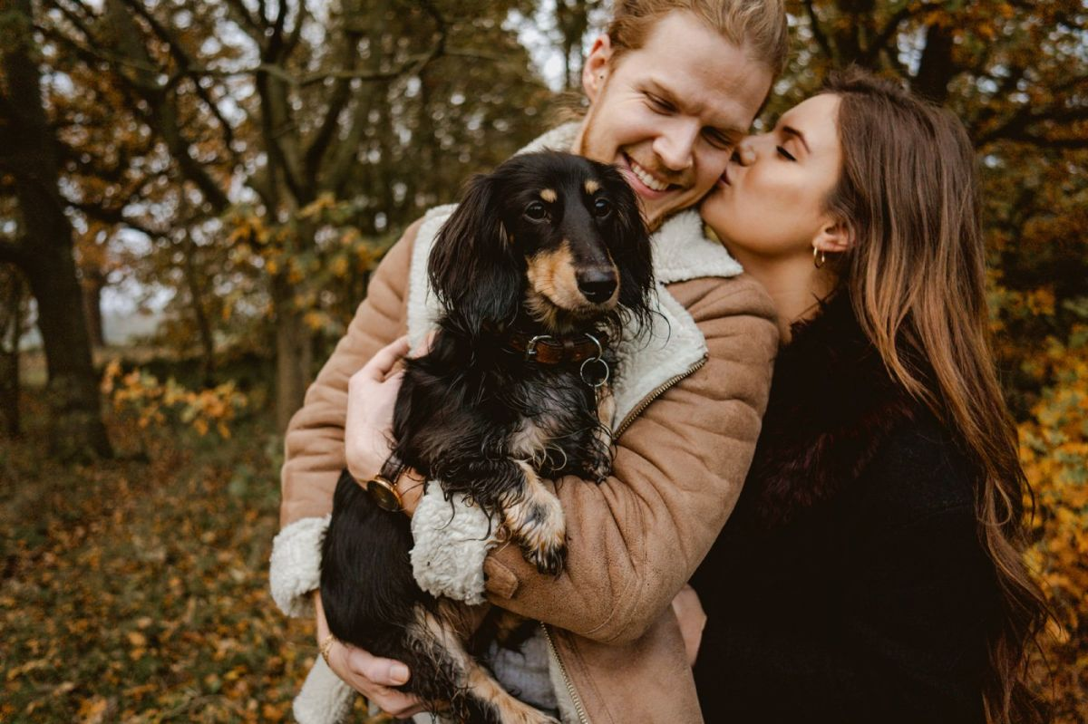 couple kissing with sausage dog