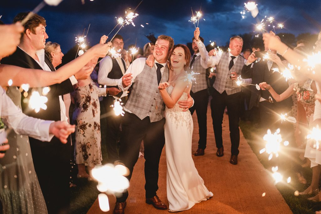 bride and groom cheer with sparklers at their Garden marquee wedding in the midlands